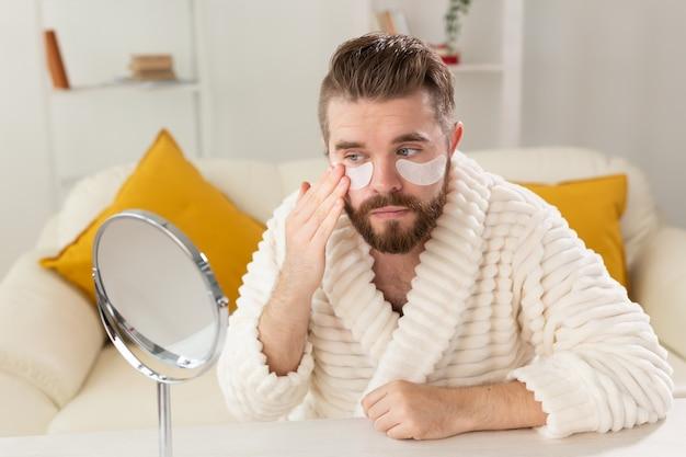 Бородатый мужчина, прикладывая повязки для глаз на лице. уход за морщинами и лицом в домашних условиях для мужчин.