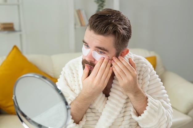 Бородатый мужчина наносит повязки на глаза на морщины и уход за лицом в домашних условиях для мужчин