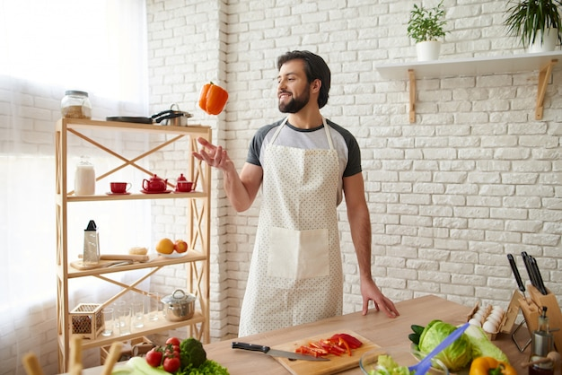 Bearded man in apron tosses up orange pepper into air.