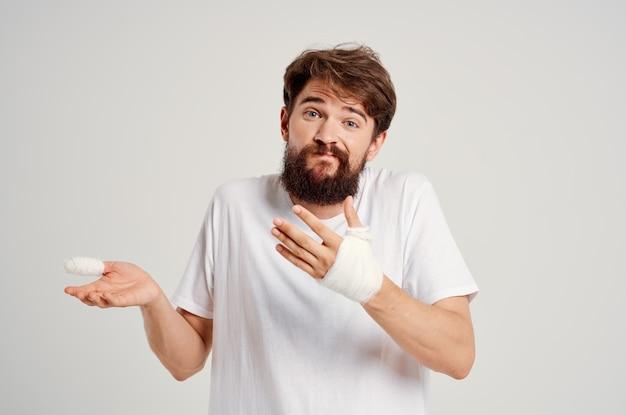 Bearded man bandaged hand injury to fingers hospitalization isolated background
