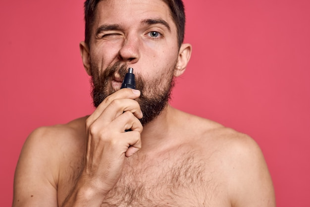 Bearded man bare shoulders removes hair from nose body care pink space