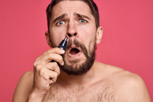 Bearded man bare shoulders removes hair from nose on a pink background