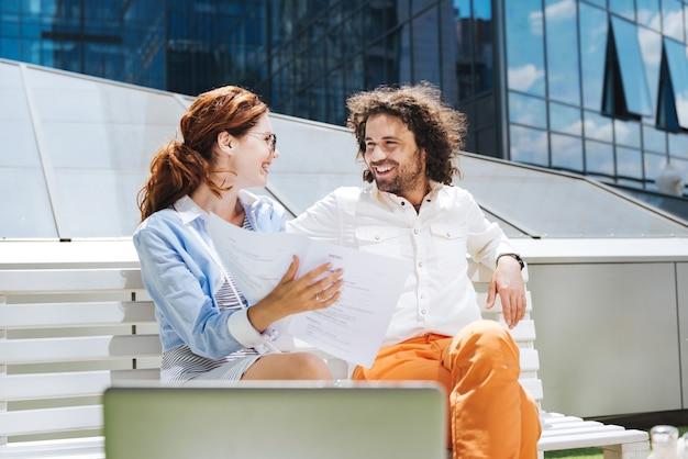 수염 난 남자. 그 근처에 앉아있는 그의 아름다운 여자와 이야기하면서 넓게 웃고 수염 난 곱슬 남자
