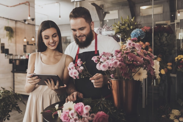 Bearded man and beautiful girl are looking tablet