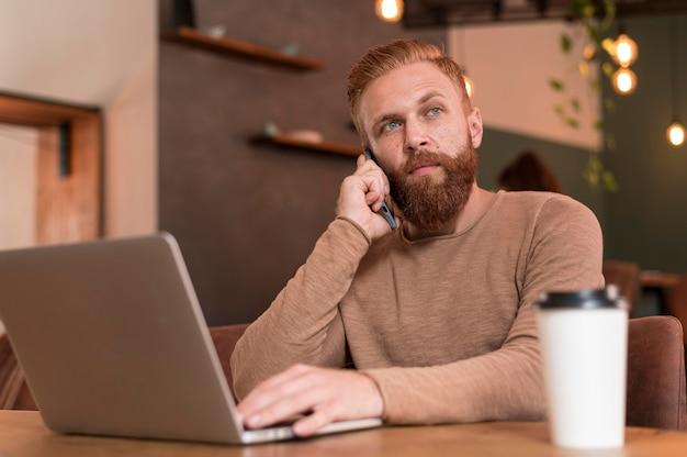 Uomo barbuto premuroso mentre si lavora