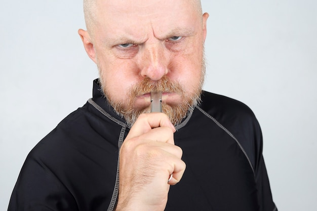 Bearded man in a black jacket blowing a whistle