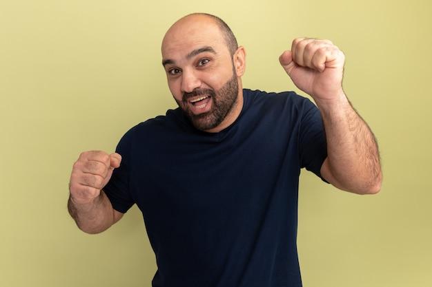 Uomo barbuto in maglietta nera pazzo felice ed eccitato urlando pugni di serraggio in piedi sopra la parete verde