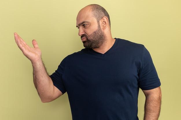 Uomo barbuto in maglietta nera che osserva da parte confuso e dispiaciuto alzando la mano con dispiacere in piedi sopra il muro verde