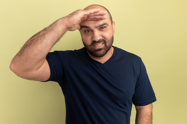 Uomo barbuto in maglietta nera che guarda lontano con la mano sopra la testa sorridente confuso in piedi sopra la parete verde