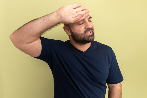 Uomo barbuto in maglietta nera che sembra stanco e infastidito con la mano sulla fronte in piedi sopra il muro verde