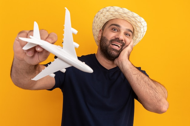Uomo barbuto in maglietta nera e cappello estivo che tiene aeroplano giocattolo stupito e sorridente felice allegramente in piedi sopra la parete arancione