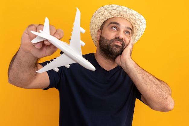 Uomo barbuto in maglietta nera e cappello estivo che tiene aeroplano giocattolo guardando perplesso in piedi sopra la parete arancione