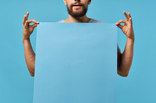 Бородатый мужчина синий баннер в руке пустой лист copyspace studio
