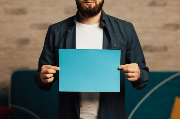 Bearded man in blue shirt holding blue empty paper with copy space in hands.
