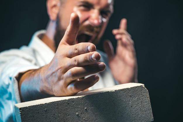 ひげを生やした男が手でコンクリートスラブを壊すひげを生やした男が空手を訓練する
