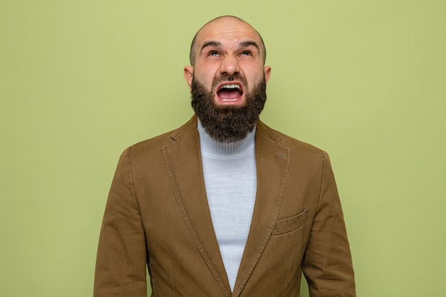 Bearded man in brown suit looking up shouting with aggressive expression