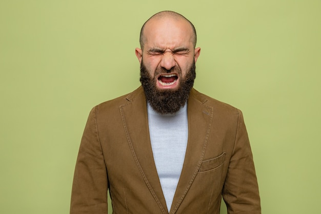 Uomo barbuto in abito marrone che grida e urla pazzo pazzo e frustrato