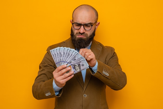 Bearded man in brown suit wearing glasses holding cash looking at money with serious face standing over orange background
