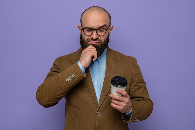 Bearded man in brown suit wearing glasses holding coffee cup looking at it puzzled standing over purple background