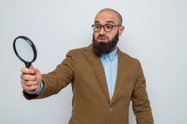 Bearded man in brown suit wearing glasses holding magnifying glass looking through it confused standing over white background