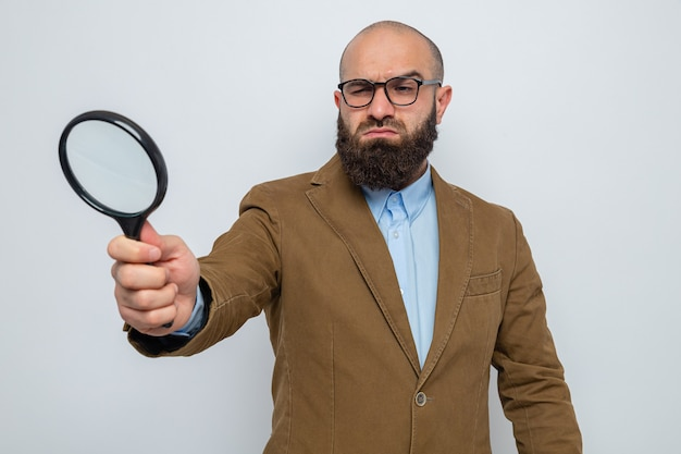 Bearded man in brown suit wearing glasses holding magnifying glass looking through it with serious face standing over white background