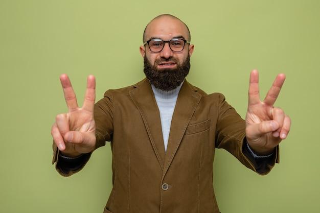 Uomo barbuto in abito marrone con gli occhiali che guarda la macchina fotografica felice e allegro sorridente che mostra ampiamente il v-sign in piedi su sfondo verde