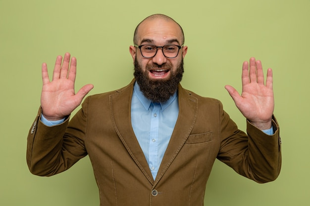 Bearded man in brown suit wearing glasses looking at camera happy and excited raising arms standing over green background
