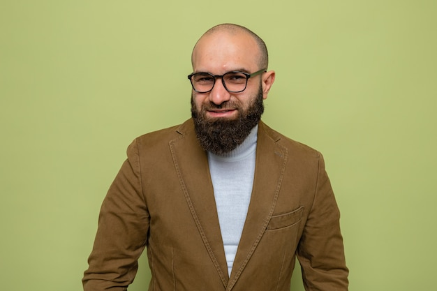 Bearded man in brown suit wearing glasses looking with smile on happy face