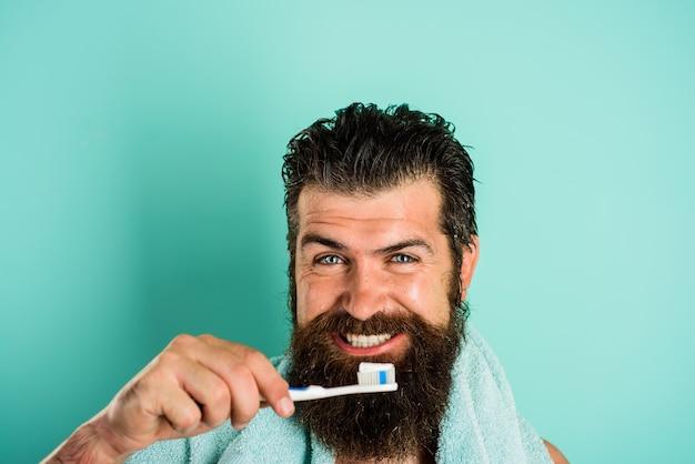ひげを生やした男が歯を磨く。歯ブラシ。歯磨き粉。朝のトリートメント。毎朝の日課。健康管理。歯科衛生。