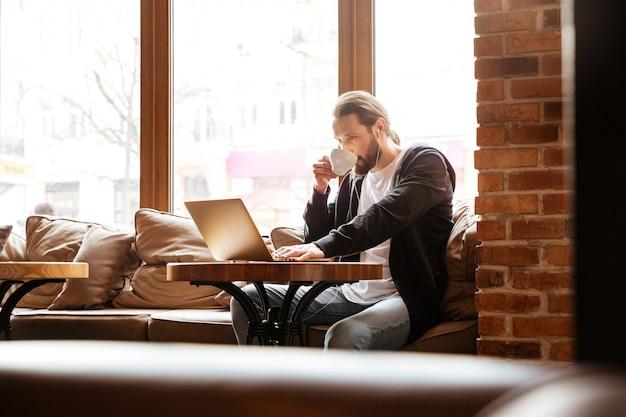Uomo barbuto nella caffetteria con laptop e caffè