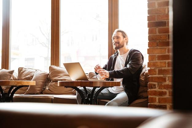 Uomo barbuto nella caffetteria con il computer portatile