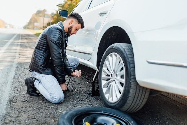 Uomo barbuto che cambia la gomma della sua auto