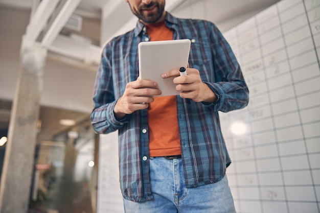 Bearded man in checkered shirt holding electronic pad pc and marker pen
