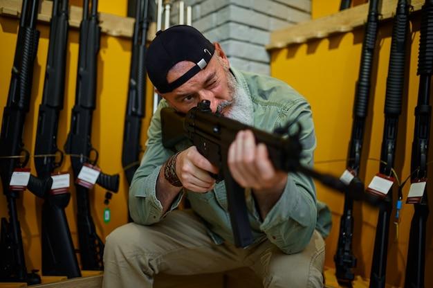 ひげを生やした男が銃店でライフルスコープをチェックします。武器屋のインテリア、弾薬と弾薬の品揃え、銃の選択、射撃の趣味とライフスタイル、護身術