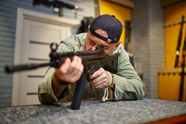 ひげを生やした男が銃店でライフルスコープをチェック