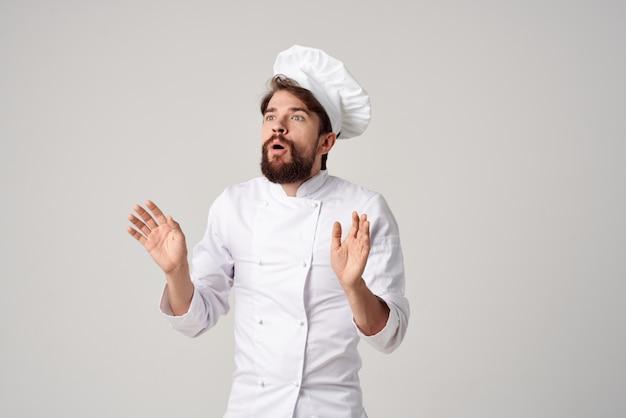 Бородатый мужчина шеф-повар готовит профессиональные эмоции кулинарной индустрии