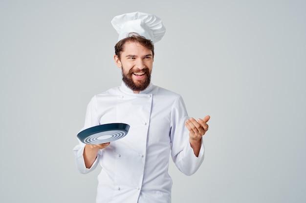 手料理業界でフライパンを持ったひげを生やした男のシェフ。高品質の写真