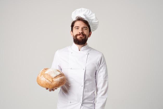 手に明るい背景のパンとひげを生やした男のシェフ