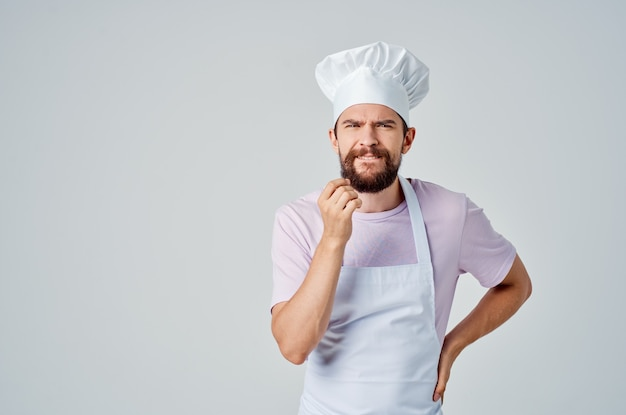 A bearded man in a chefs uniform gestures with his hands the emotions of professionals