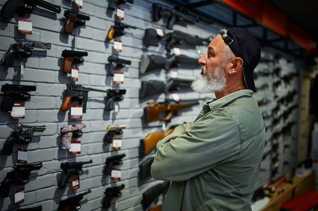 銃店のショーケースでピストルを選ぶひげを生やした男。武器屋のインテリア、弾薬と弾薬の品揃え、銃器の選択、射撃の趣味とライフスタイル、護身術