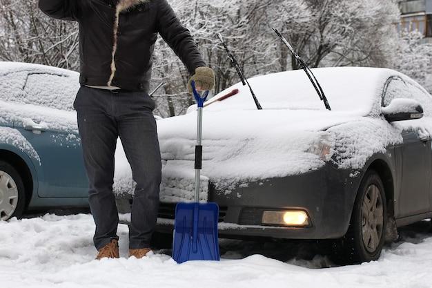 수염 난 남자는 겨울 아침에 차에서 눈을 청소