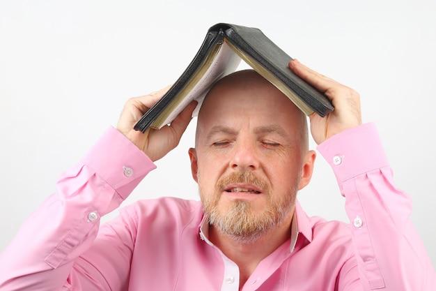 수염 난된 남자가 열린 성경으로 그의 머리를 가리고