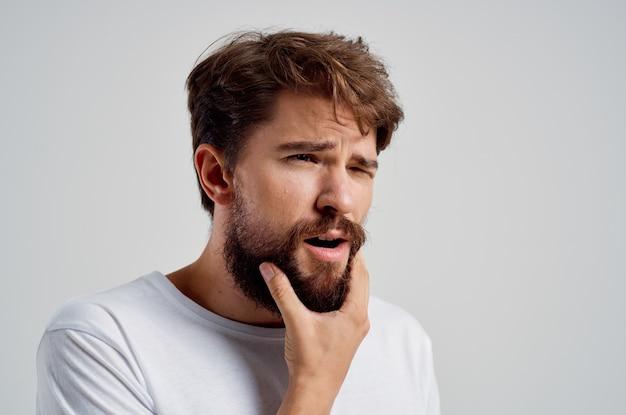 Бородатый мужчина стоматологическая проблема лечение стоматологии светлый фон