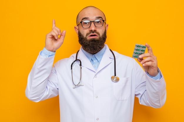 Бородатый мужчина-врач в белом халате со стетоскопом на шее в очках, держащий блистер с таблетками, удивленно смотрит вверх, показывая указательный палец, имеющий новую идею, стоящий на оранжевом фоне