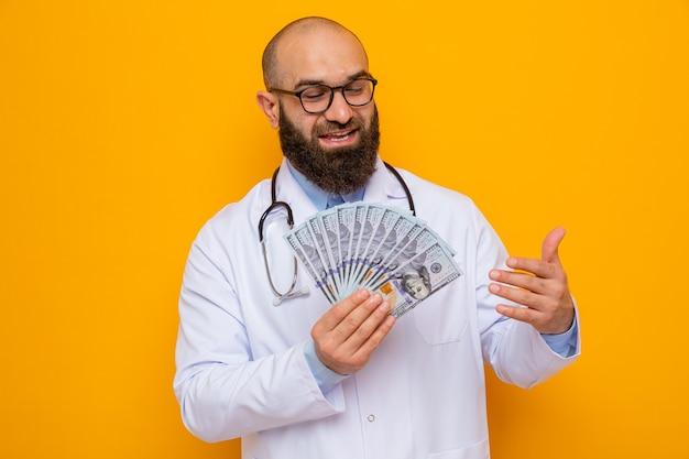 Бородатый мужчина-врач в белом халате со стетоскопом на шее в очках держит деньги счастливыми и довольными улыбками