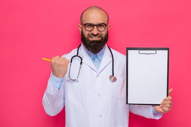 빈 페이지와 클립 보드를 들고 안경을 쓰고 목 주위에 청진기와 흰색 코트에 수염 난 남자 의사가 행복하고 흥분된 주먹을 떨리는 유쾌하게 웃고