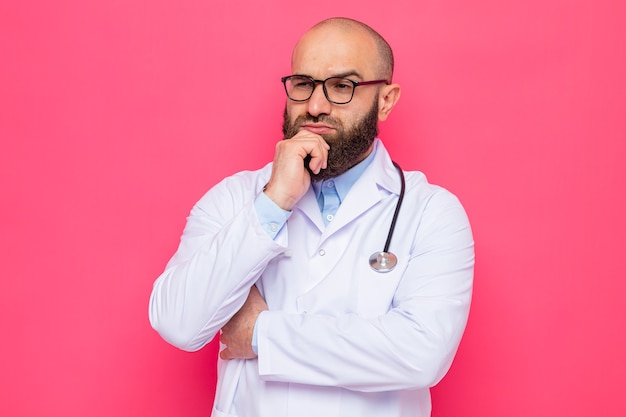 白衣を着たひげを生やした男性医師、首に聴診器を装着し、あごに手を当てて物思いにふける表情で脇を向いている眼鏡をかけている