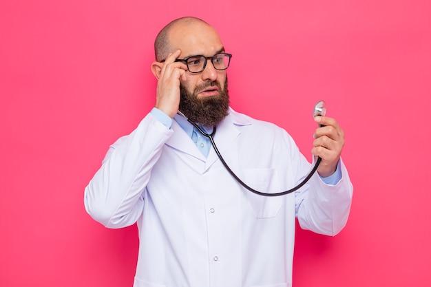 Uomo barbuto medico in camice bianco con gli occhiali con uno stetoscopio guardandolo stupito in piedi su sfondo rosa