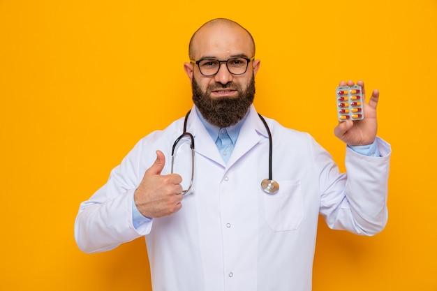 Uomo barbuto medico in camice bianco con stetoscopio intorno al collo con gli occhiali che tengono blister con pillole guardando la telecamera sorridendo allegramente mostrando i pollici in piedi su sfondo arancione