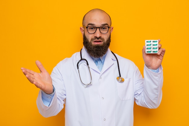 Bearded man doctor in white coat with stethoscope around neck wearing glasses holding blister with pills looking happy and surprised raising arm
